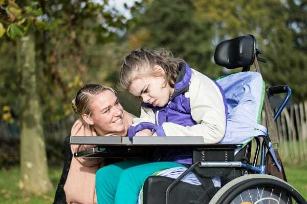 Disabled girl in a wheelchair relaxing outside / Disabled girl in a wheelchair relaxing outside together with a care assistant
